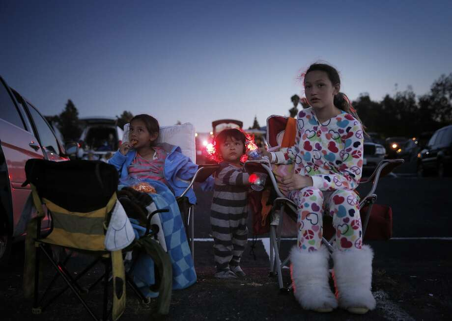 "Jasmine Guerrero, 7, left, Gene Martinez, 18 mos, center, and Isabelle Martinez, 12, right, watch ""Inside Out "" at the West Wind Solano 2 drive-in theater in Concord, Calif., on Sunday, June 28, 2015. Drive-in theaters are a special breed of theater where patrons set up tables, deck chairs, even couches and watch the movie while seated outside, or from the back of a lifted hatch on an SUV. The sound is on FM radio frequencies so those old boxes attached to the window no longer exist. Photo: Carlos Avila Gonzalez, The Chronicle"