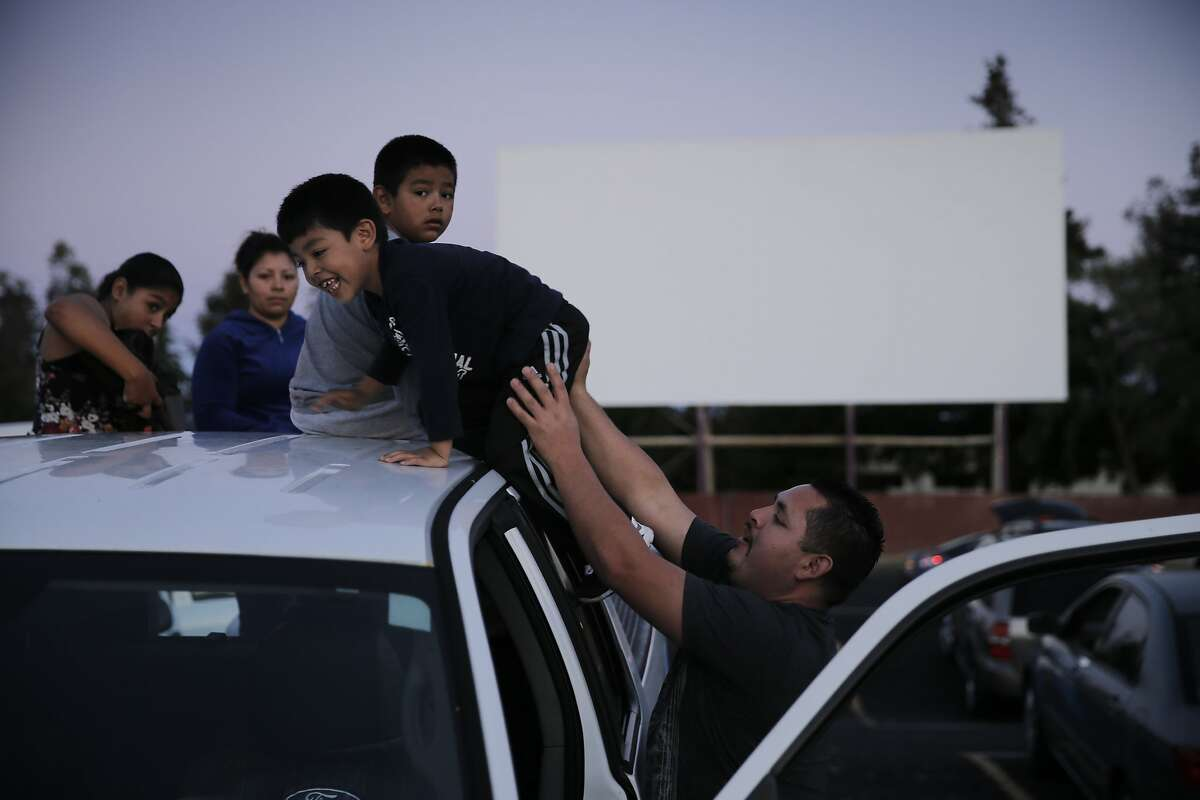 Gerardo Montaño pushes up his son Brandon, 5, onto the roof of his truck to join his brother Emanuel, 8, before watching Jurassic World at the West Wind Solano 2 drive-in theater in Concord, Calif., on Sunday, June 28, 2015. Drive-in theaters are a special breed of theater where patrons set up tables, deck chairs, even couches and watch the movie while seated outside, or from the back of a lifted hatch on an SUV. The sound is on FM radio frequencies so those old boxes attached to the window no longer exist.