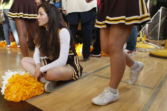 Tonantzin Alcantar, a cheerleader for the Mission High School Bears basketball team, sits on the court in between periods during a game against the June Jordan School of Equity at Mission High School in San Francisco, Calif. Friday, February 27, 2015.
