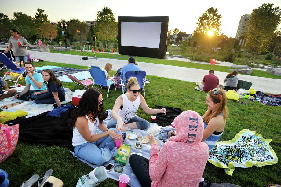 """Mill River Park in Stamford, Conn., again will offer free outdoor movie series for the summer of 2015. Movies in the Park kicks off with """"Jurassic Park"""" on Friday, July 3, 2015. Here, a crowd enjoys the festivities in 2013, before the showing of the movie """"Jaws."""" From left, clockwise, Caitlin Moseley, Ashley Edelman, Sarah Michalka and Jessica Mossa play a card game. Photo: Jason Rearick / File Photo / Stamford Advocate"""