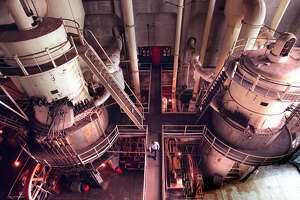 1997: Lilly Tellefson, center, is dwarfed by huge machinery as she walks through the old Georgetown Steam Plant on Feb. 17, 1997. Photo by Kurt Smith, Seattle Post-Intelligencer.