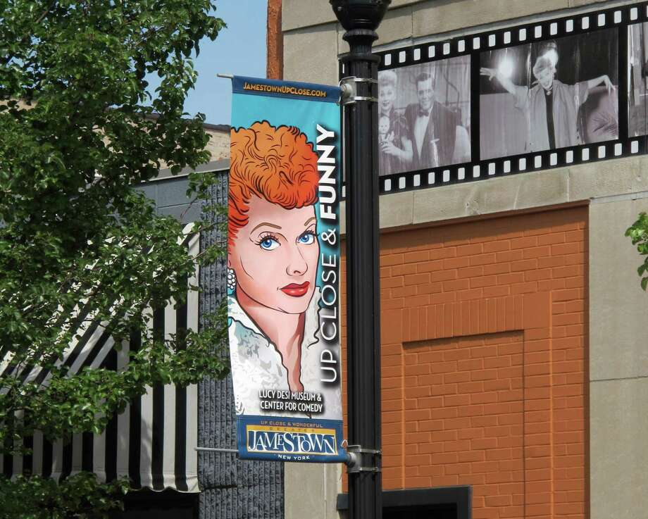 In this June 26, 2015 photo, a banner hangs outside the Lucille Ball-Desi Arnaz Museum in Ball's hometown of Jamestown, N.Y. The nonprofit National Comedy Center Inc., which runs the museum, plans to break ground this summer on the National Comedy Center to be located nearby. The national center will explore the art and science of comedy across all platforms and generations. (AP Photo/Carolyn Thompson) Photo: Carolyn Thompson, STF / AP