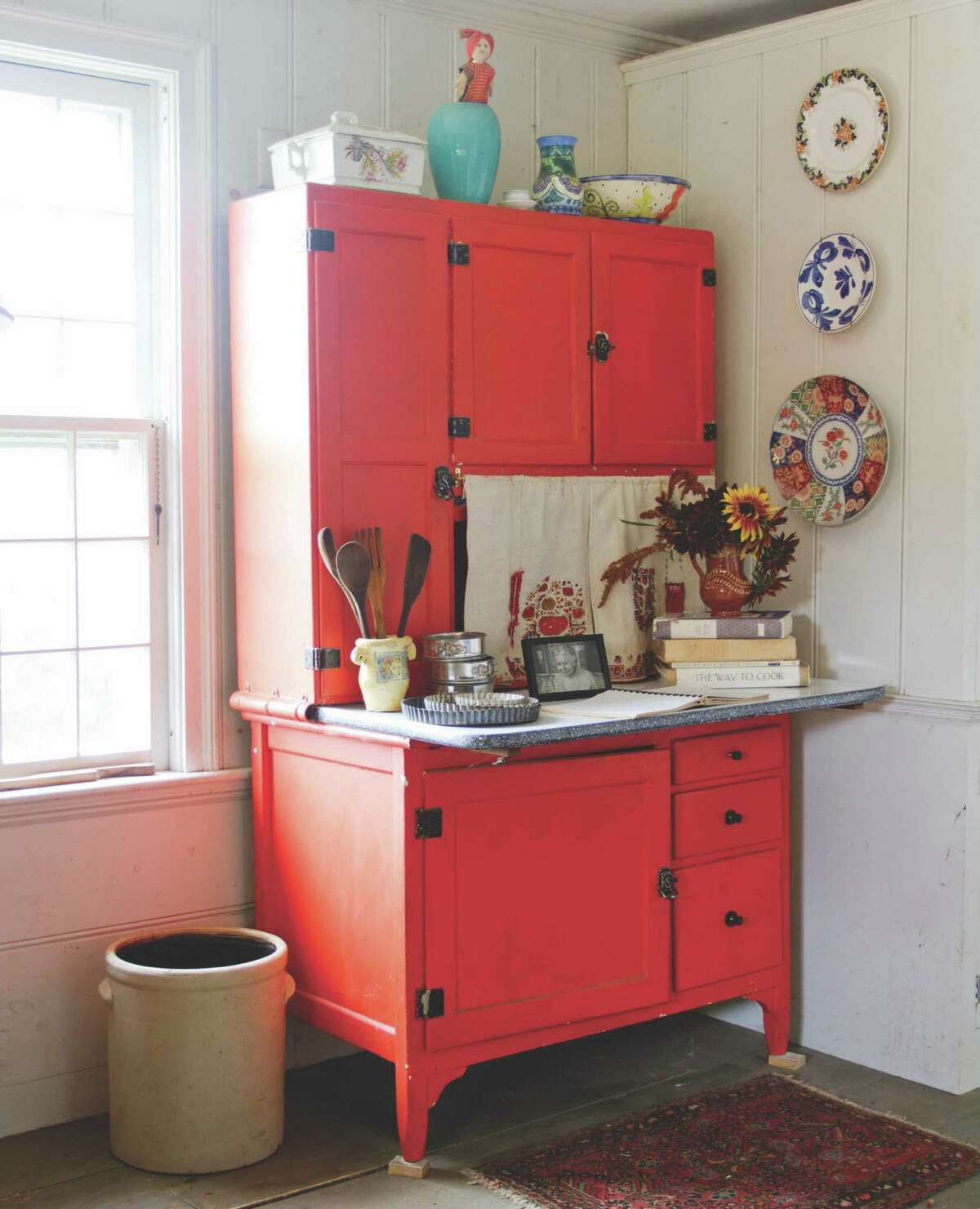 One bold piece of furniture can brighten a room. Kristin Nicholas designed her kitchen around this antique cupboard, painted red. Colorful plates on the wall add shades of blue, green and more.