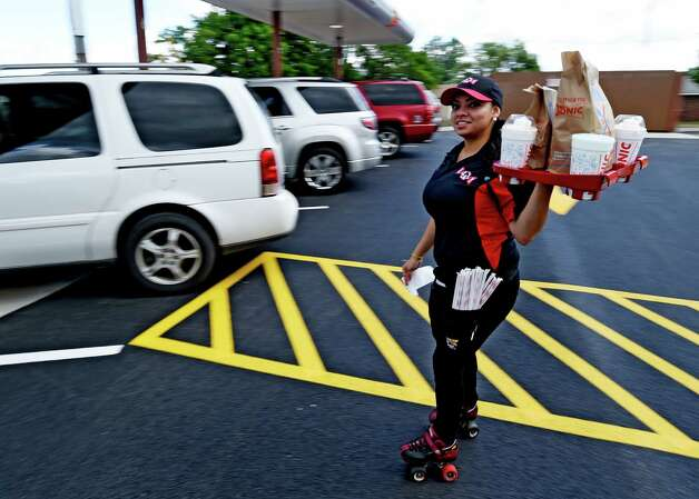 Carhop Carolina Estrade moves swiftly across the parking lot to deliver an order at the new Sonic Monday, June 29, 2015, during the soft opening of the franchise in Latham, N.Y.  (Skip Dickstein/Times Union) Photo: SKIP DICKSTEIN / 00032420A