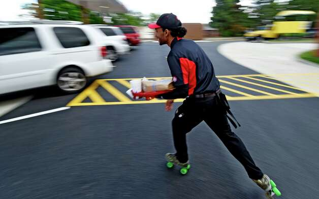 Carhop Sean Little moves swiftly across the parking lot to deliver an order at the new Sonic Monday, June 29, 2015, during the soft opening of the franchise in Latham, N.Y.  (Skip Dickstein/Times Union) Photo: SKIP DICKSTEIN / 00032420A