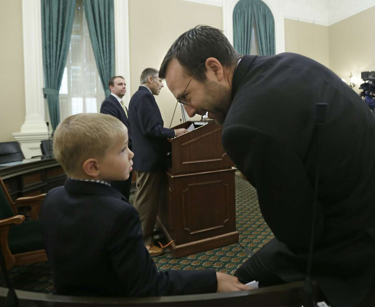 Leukemia survivor Rhett Krawitt, 7, talks with Sen. Ben Allen, D-Santa Monica, who is the co-author of a measure requiring nearly all California school children to be vaccinated, at a news conference at the Capitol in Sacramento, Calif., Wednesday, June 24, 2015. Rhett, who was unable to be vaccinated while receiving treatment for his Leukemia, was accompanied by his father, Carl Krawitt, background center, delivered a box of petitions representing some of the over 30,000 signatures asking for lawmakers to approve SB277 and the Governor to sign it. The state Assembly is expected to vote on the bill, Thursday. (AP Photo/Rich Pedroncelli)