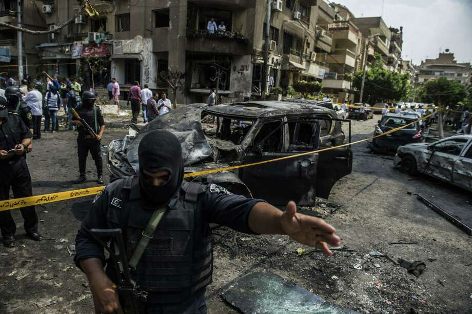 Egyptian security forces stand guard at the site of a bomb attack that targeted the convoy of Egyptian state prosecutor, Hisham Barakat, who died hours after the powerful explosion hit his convoy, in the capital Cairo on June 29, 2015. The bombing came after the Islamic State group's affiliate in Egypt called for attacks on the judiciary following the hanging of six alleged militants. AFP PHOTO / KHALED DESOUKIKHALED DESOUKI/AFP/Getty Images Photo: KHALED DESOUKI, Staff / AFP / Getty Images / AFP