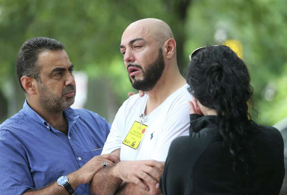Emad Alhalqaqah comforts Eyed Naim, brother of road rage shooting victim Ziad Abu Naim, after a press conference Monday. Photo: Mayra Beltran, Staff / © 2015 Houston Chronicle