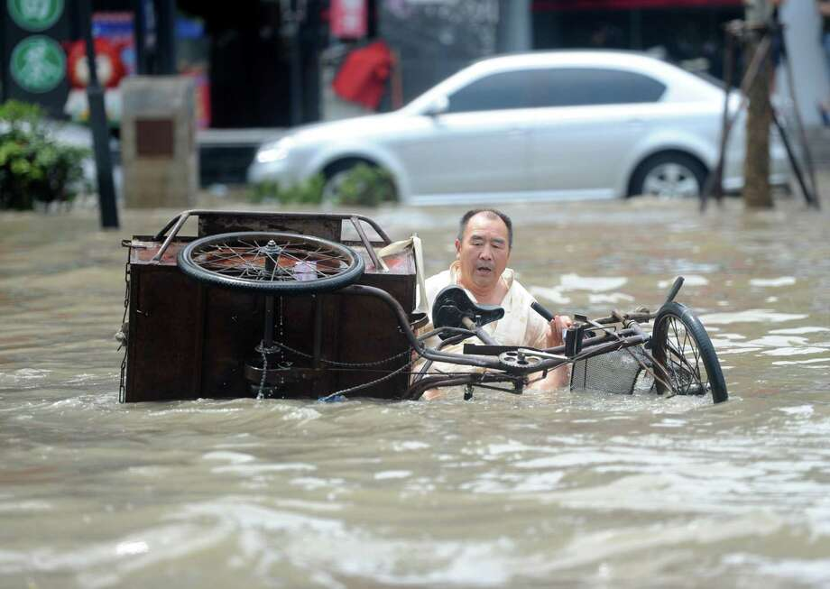HUAINAN, CHINA - JUNE 29:  (CHINA OUT) A man falls off a tricycle in a flooded street on June 29, 2015 in Huainan, China. Torrential rains swept parts of the provinces of Henan, Hubei, Anhui, Jiangsu and Zhejiang this weekend, leaving at least seven people dead, according to local authorities.  (Photo by ChinaFotoPress/ChinaFotoPress via Getty Images) Photo: ChinaFotoPress, Stringer / 2015 Getty Images