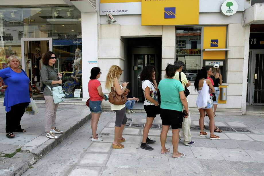 Anxious Greeks line up at an ATM in Athens  for their daily cash allowance  of 60 euros ($67) each. People were also emptying supermarket shelves and filling up containers at gas stations. Photo: Thanassis Stavrakis, STF / AP