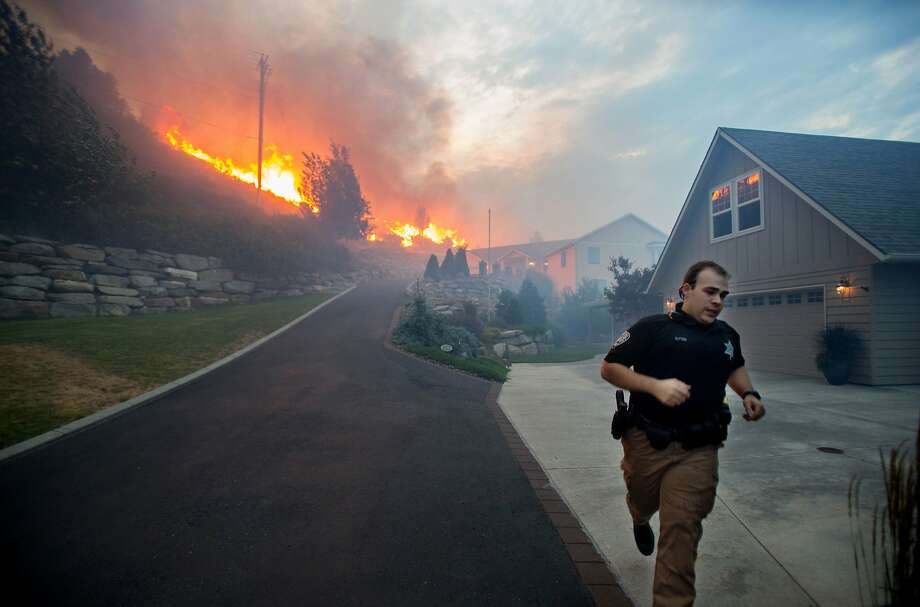 A Chelan County Sheriff's deputy races to check that all residents have left their home as flames approach houses at Quail Hollow Lane in Wenatchee, Wash. A wildfire fueled by high temperatures and strong winds roared into the central Washington neighborhood, destroying properties and forcing residents of several hundred homes to flee, authorities said Monday. Photo: Don Seabrook, Associated Press