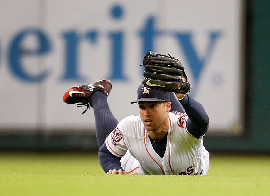 Astros right fielder George Springer (4) makes a diving catch of a line drive by Royals center fielder Lorenzo Cain during the third inning Monday night. Cain went 0-for-4 on the night. Photo: Karen Warren, Staff / © 2015 Houston Chronicle