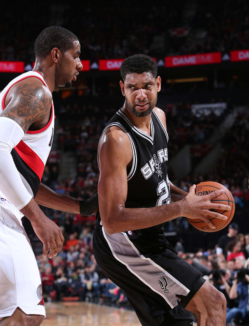 PORTLAND, OR - FEBRUARY 25: Tim Duncan #21 of the San Antonio Spurs handles the ball against LaMarcus Aldridge #12 of the Portland Trail Blazers on February 25, 2015 at the Moda Center Arena in Portland, Oregon. NOTE TO USER: User expressly acknowledges and agrees that, by downloading and or using this photograph, user is consenting to the terms and conditions of the Getty Images License Agreement. Mandatory Copyright Notice: Copyright 2015 NBAE (Photo by Sam Forencich/NBAE via Getty Images)