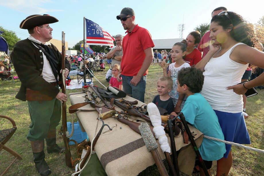 Scott Matty (left) shows reproductions of weapons used by the military, militia and Continental Army in the Revolutionalry War to a gathering during Helotes' Independence Day Celebration at the Municipal Complex at City Hall on Saturday, July 5, 2014.  The event included free hot dogs, apple pie and Blue Bell ice cream as well as other food and refreshments, a concert by the Helotes Area Community Band and a spectacular fireworks display.  MARVIN PFEIFFER/ mpfeiffer@express-news.net Photo: MARVIN PFEIFFER, STAFF / Marvin Pfeiffer/ EN Communities / Express-News 2014