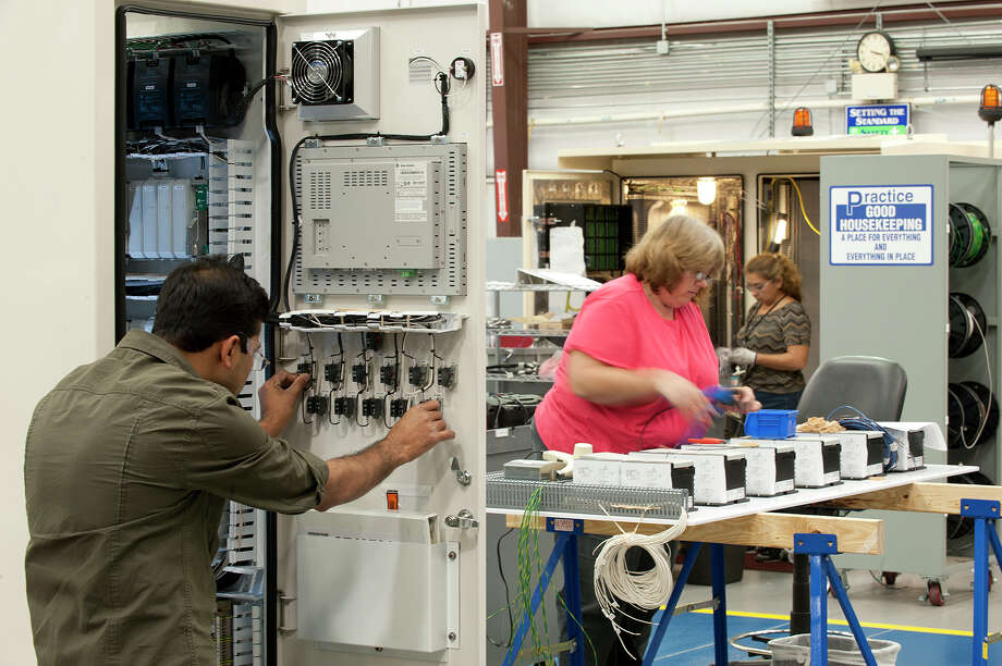 Workers assemble a control panel at Dresser-Rand. / ONLINE_YES