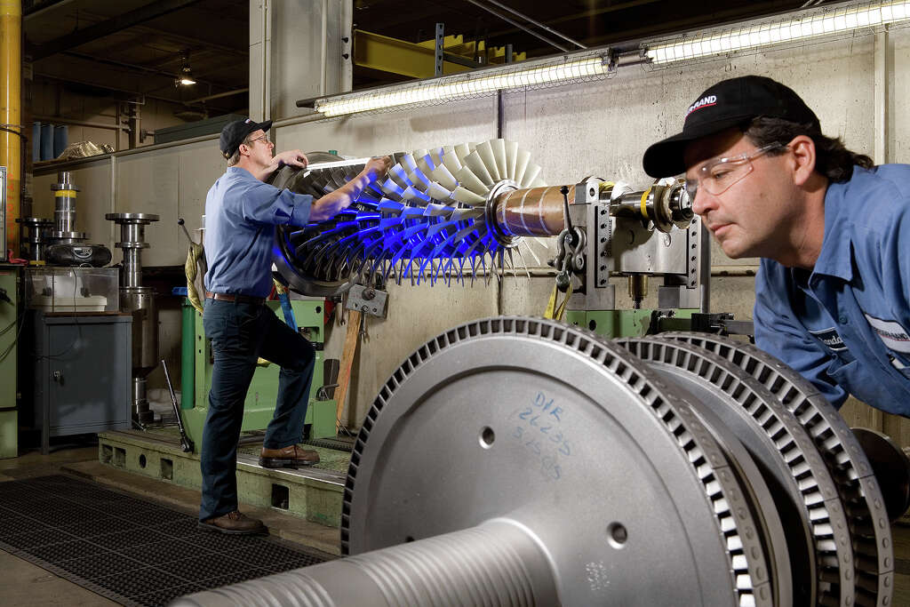 Workers Balance And Inspect Compressor Steam Turbine Rotors At Dresser Rand Photo