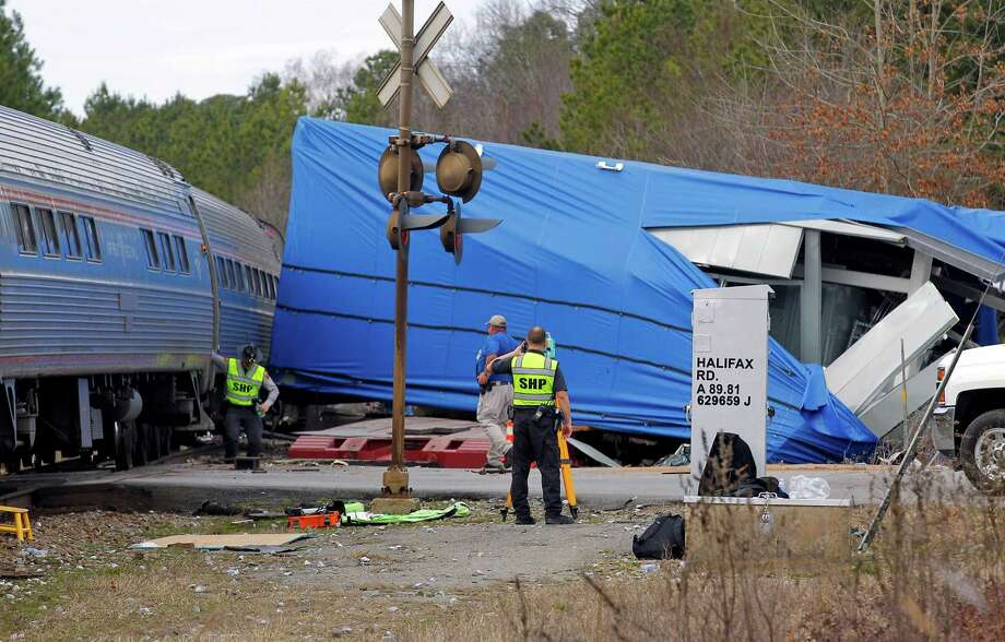 FILE - This March 9, 2015 file photo, a northbound Amtrak train collided with an oversized truck carrying an electrical building when the truck got stuck on the tracks at an intersection in Halifax, NC. The federal agency that oversees railroads is asking digital mapping companies to alert users as they approach track crossings. The Federal Railroad Administration announced Monday, June 29, that, so far, Google has agreed. (Chris Seward/The News & Observer via AP, File) Photo: Chris Seward, MBO / The News and Observer