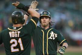 OAKLAND, CA - JUNE 29:  Josh Reddick #22 of the Oakland Athletics is congratrulated by Stephen Vogt #21 on his two-run homer against the Colorado Rockies in the bottom of the first inning at O.co Coliseum on June 29, 2015 in Oakland, California.  (Photo by Thearon W. Henderson/Getty Images)