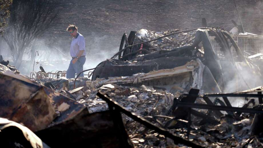 Vern Smith walks through the rubble of his still smoldering home, destroyed in a wildfire the night before, Monday, June 29, 2015, in Wenatchee, Wash. The wildfire fueled by high temperatures and strong winds roared into town Sunday afternoon. The blaze ignited in brush just outside Wenatchee, quickly burning out of control. Photo: Elaine Thompson, Associated Press / AP