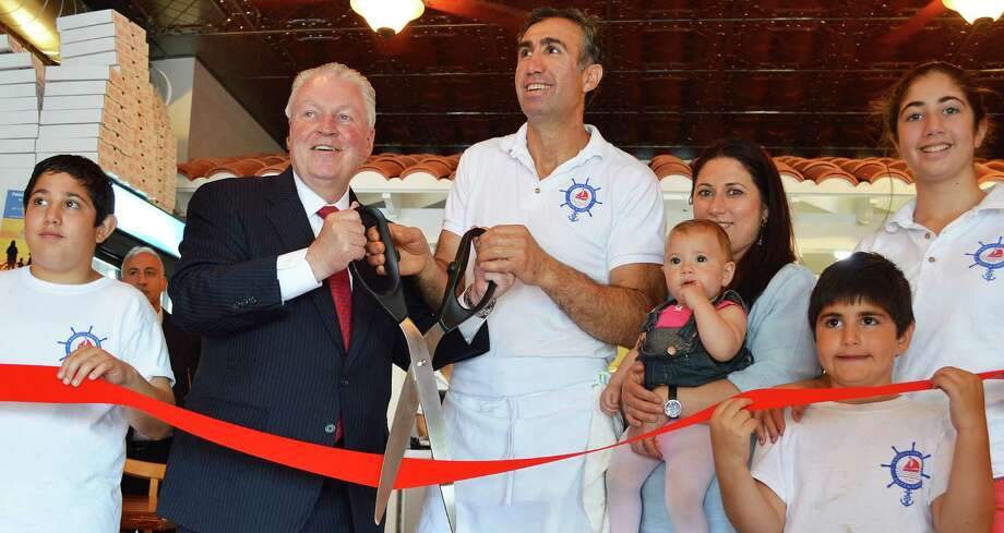 Sammy's Pizza and Grill in Southport Village reopened Monday after being closed since an April 2014 fire. At the ribbon-cutting owner Sammy Palik, center, was joined by First Selectman Michael Tetreau and his family. Photo: Jarret Liotta / For Hearst Connecticut Media / Fairfield Citizen