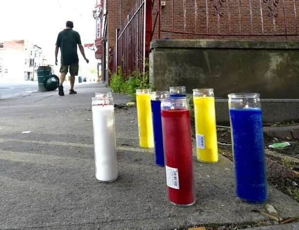 Mourners have placed candles near the Albany Street, Schenectady, site where a man was gunned down late Monday night. The 11 p.m. shooting happened near Zaid's Food Market, 807 Albany St. (Skip Dickstein / Times Union)