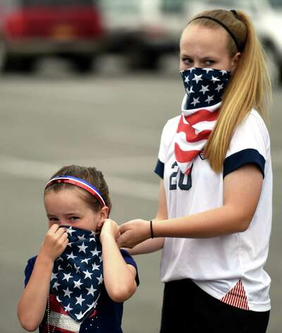 Chelsea Ralston, 7, left, is helped with her bandana by big sister Taylor Ralston, 13, at Crossgates Commons Tuesday morning, June 30, 2015, in Albany, N.Y., as they prepare for a trip to Montreal to watch Team USA Women's soccer compete tonight in the World Cup. (Skip Dickstein/Times Union) Photo: SKIP DICKSTEIN / 00032412A