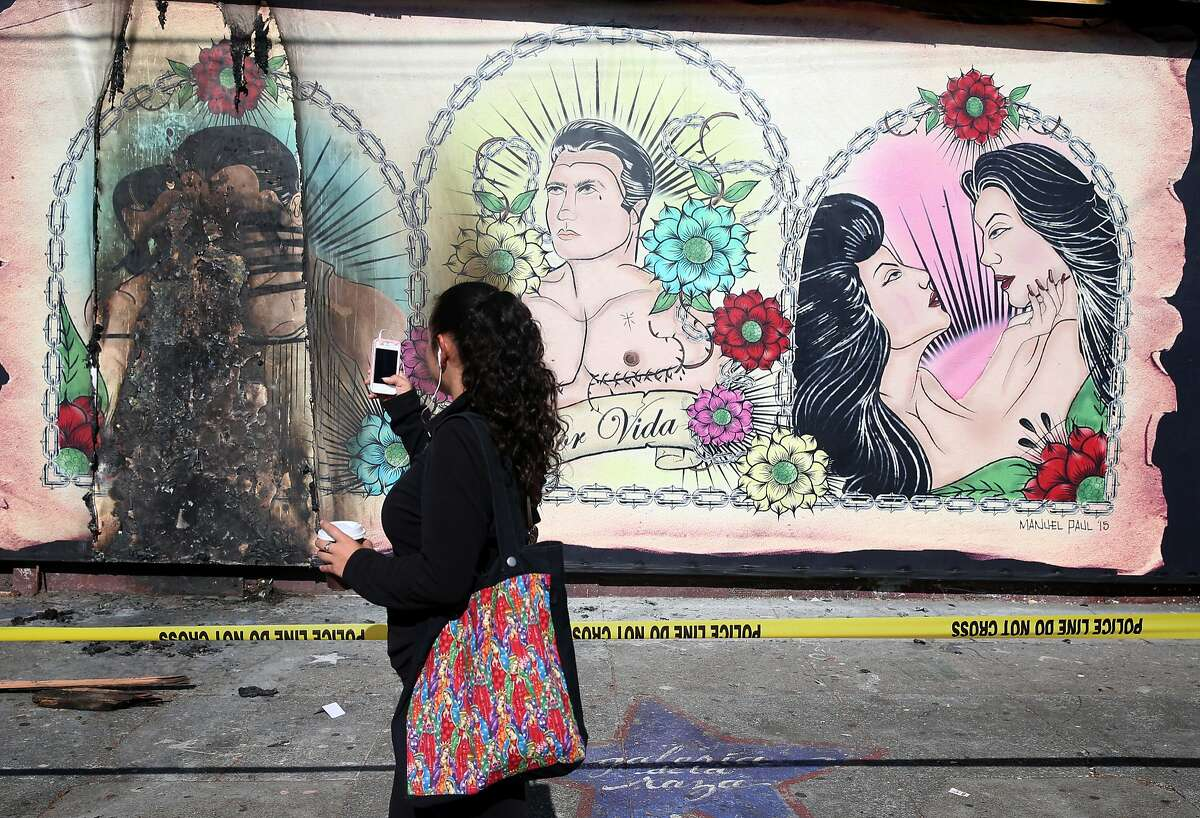 Jessina Mendoza records a charred portion of a mural at Galeria de la Raza in San Francisco, Calif. on Tuesday, June 30, 2015 after the LGBT-themed artwork was damaged for a third time. Ani Rivera, the gallery's executive director, is deciding whether or not to replace the mural, which was scheduled to be displayed through the end of July.