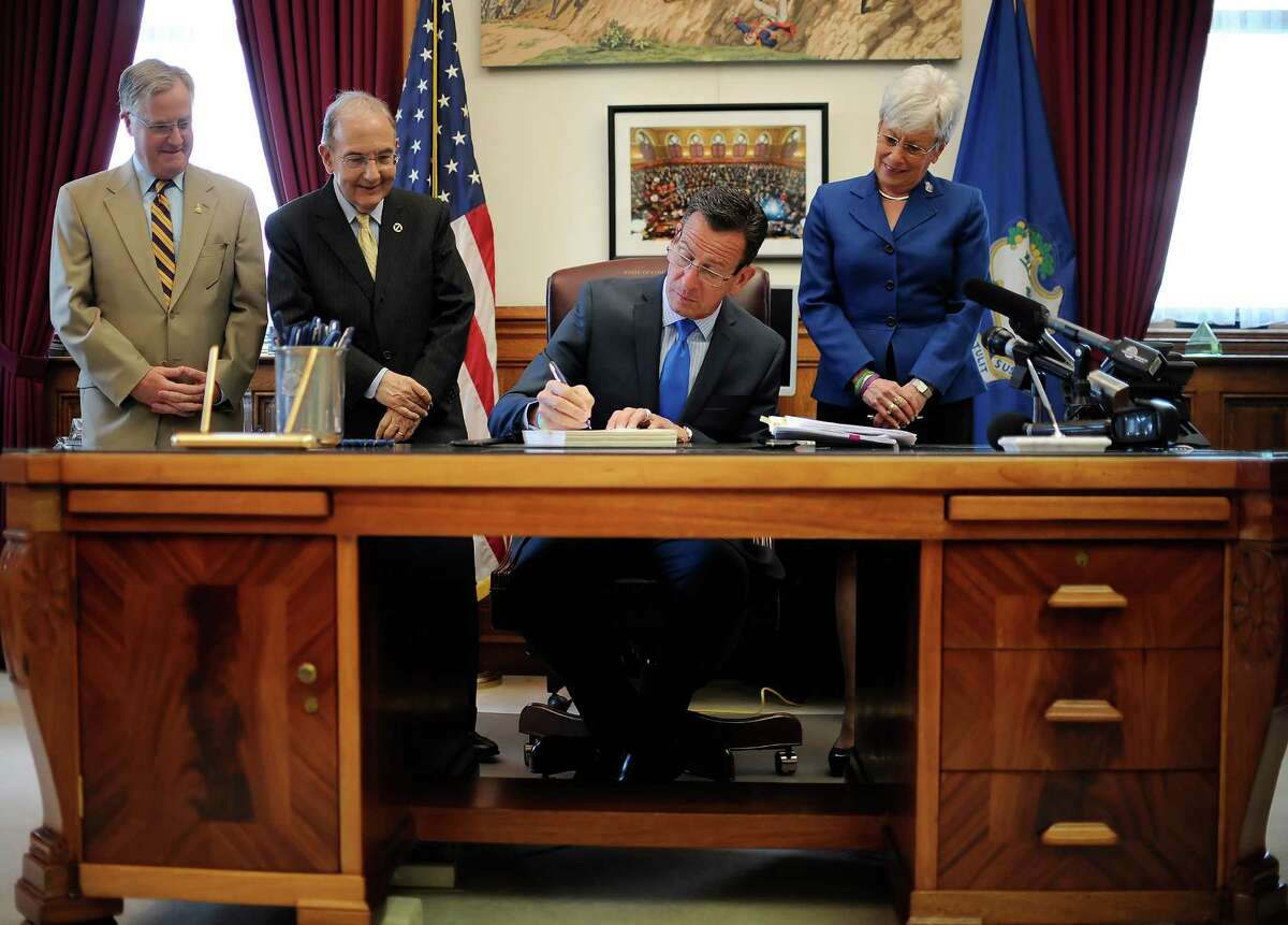 Connecticut Gov. Dannel P. Malloy, signs the budget as Speaker of the House Brendan Sharkey, left, State Senate President Martin Looney, D-New Haven, second from left and Lt. Gov. Nancy Wyman, right, looks on, in his office at the State Capitol.
