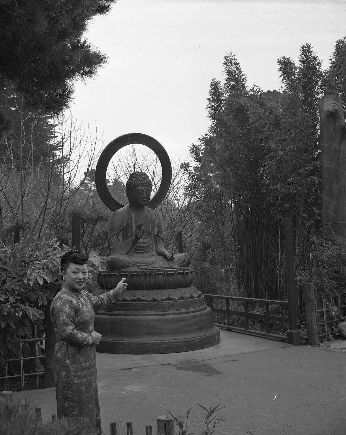 The Buddha at the Japanese Tea Garden in Golden Gate Park being installed in March 1949. It was a gift from the Gump family, and had been in their store for 15 years. The negative identifies the woman as Edna Lee photo dated 03/02/1949