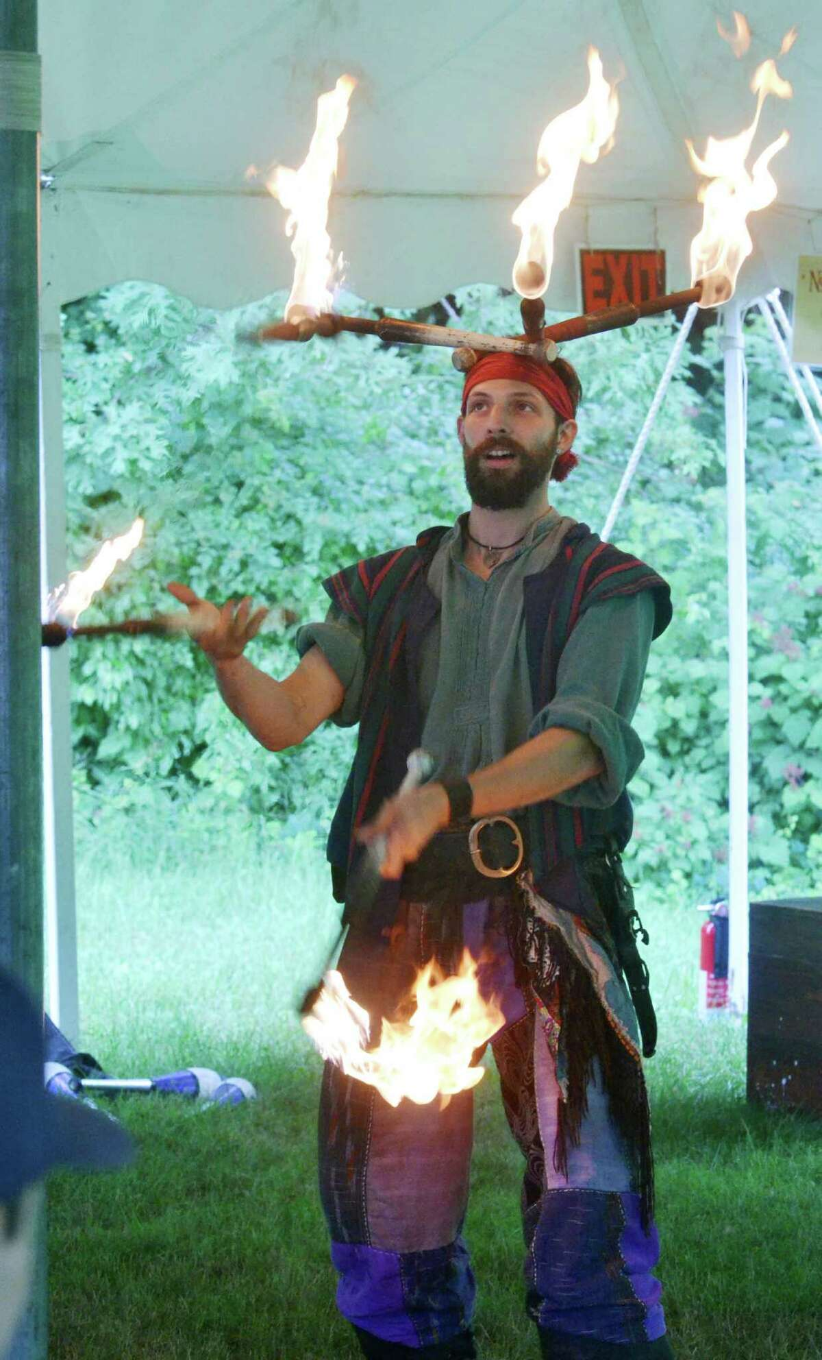 Chris Abbot, from South Plainville, N.J., balances torches on his head while simultaneously jugging fire at the Midsummer Fantasy Reinassance Faire at Warsaw Park in Ansonia, Conn. on June 28, 2015. The last weekend to visit the faire is July 4-5, 2015 from 11 a.m to 6:30 p.m.