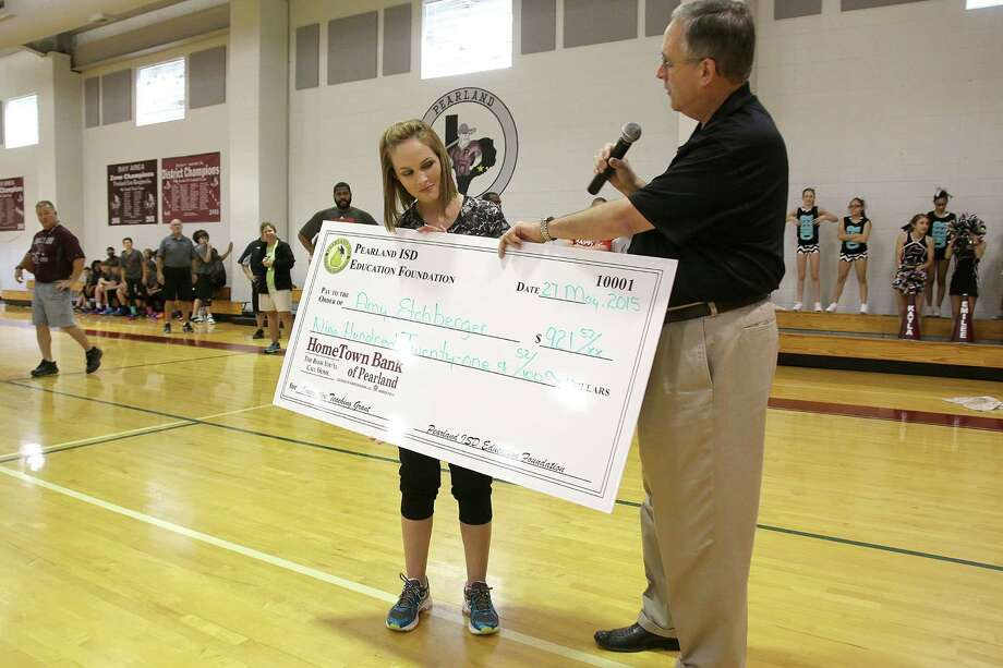 Kyle Ford, a board member on the Pearland ISD Education Foundation, presents a check for $921.52 to Amy Etchberger of Pearland Junior High East. In its second year, the foundation is seeking to follow the success of other nonprofit groups in the area that provide funding for education programs in public schools through fundraisers and donations.Kyle Ford, a board member on the Pearland ISD Education Foundation, presents a check for $921.52 to Amy Etchberger of Pearland Junior High East. In its second year, the foundation is seeking to follow the success of other nonprofit groups in the area that provide funding for education programs in public schools through fundraisers and donations. Photo: Pin Lim, Freelance / Copyright Forest Photography, 2015.
