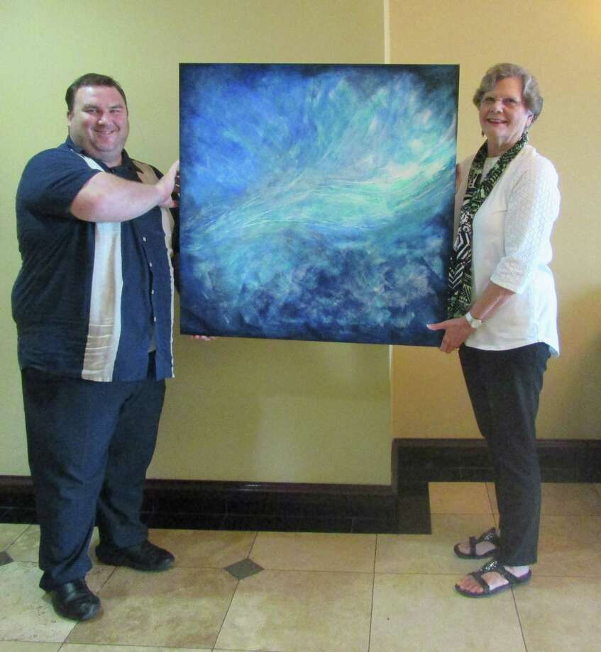 "Sheldon Green, general manager of Holiday Inn Express and Suites in Pearland, and artist Margo I. Green with her abstract painting, ""Heaven's Hand."" Green's work is on exhibit at the hotel throughout July.          Sheldon Green, general manager of Holiday Inn Express and Suites in Pearland, and artist Margo I. Green with her abstract painting, ""Heaven's Hand."" Green's work is on exhibit at the hotel throughout July. Photo: Pearland Arts League"