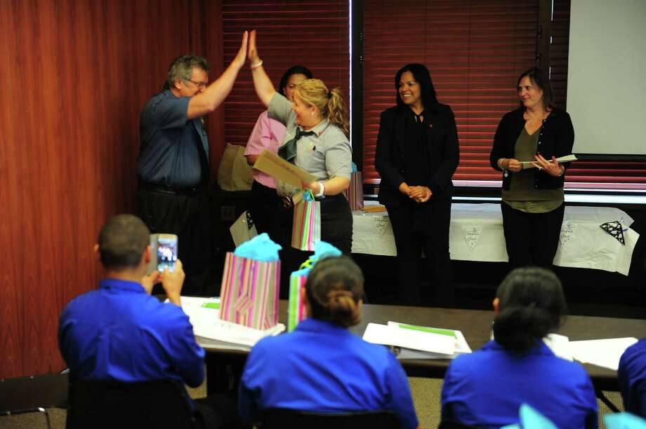 McDonald's manager Adriana Martinez high fives supervisor Gary Galgano, left, after getting her graduation certificate, as she and fellow McDonald's employees celebrate graduation from the eight week English Under the Arches (EUA) program at Trefz Corporation headquarters in downtown Bridgeport, Conn., on Thursday June 25, 2015. The program, which is specifically designed to help McDonald's employees advance in their careers, includes a four course curriculum that covers listening, speaking, reading and writing English. Trefz Corp. manages over 40 McDonald's restaurants. Photo: Christian Abraham / Hearst Connecticut Media / Connecticut Post