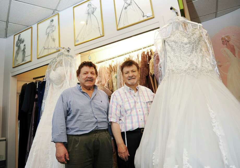 Brothers Jack, left, and Etalo CeCi pose beside a selection of wedding gowns at Exclusive Bridal Shoppe in Greenwich, Conn. Tuesday, June 30, 2015.  The family bridal shop, located at 470 W. Putnam Ave., has been a Greenwich staple for the last 50 years and specializes in custom dresses sold across the world. Photo: Tyler Sizemore / Hearst Connecticut Media / Greenwich Time