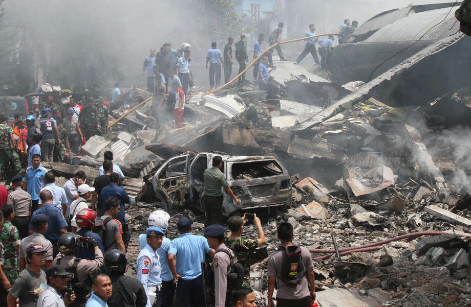 Firefighters and military personnel inspect the site where an Air Force cargo plane crashed in Medan, North Sumatra, Indonesia, on Tuesday. An Indonesian Air Force Hercules C-130 plane with 12 crew aboard crashed into a residential neighborhood in the country's third-largest city. Medan. (AP Photo/Gilbert Manullang) Photo: Gilbert Manullang, STR / AP