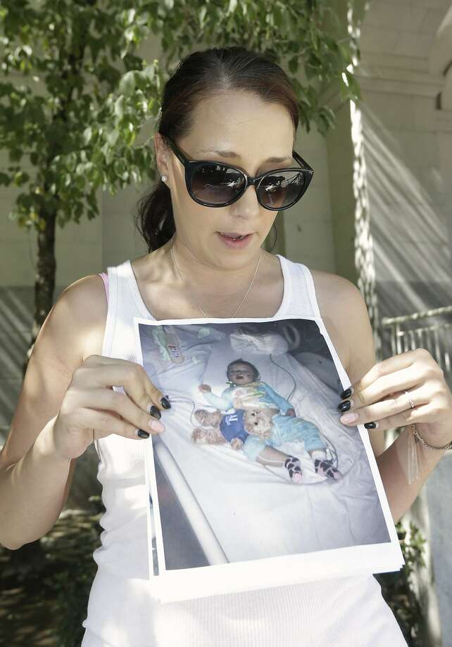 Kimberly McCauley, a foe of the vaccine measure, holds a photo of her daughter, Ella, after what McCauley says was a bad reaction to a vaccine. Photo: Rich Pedroncelli, Associated Press