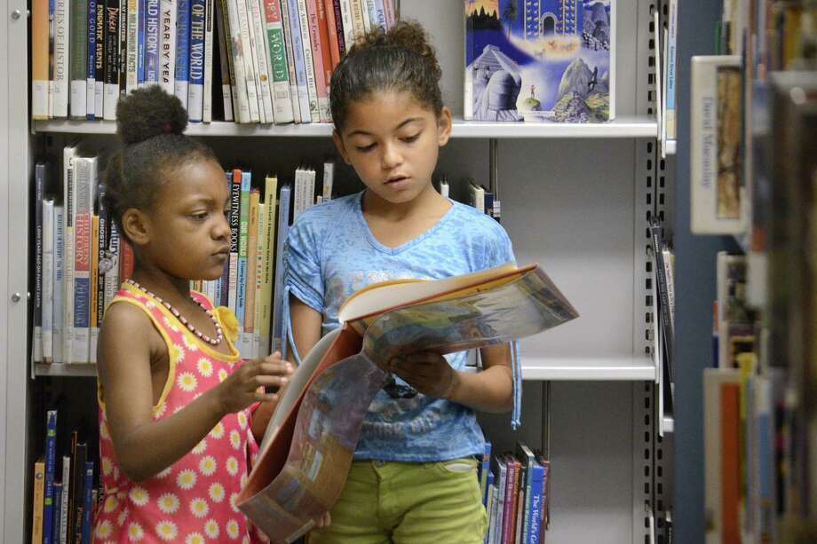 Caidyn Rogers, 9, at right, and her cousin Kourtney Willis, 6, look for books Thursday, June 4, 2015, in the Children's/Youth Services room at the Marion Public Library in Marion, Ind.  The two girls are taking part in the library's summer reading program.  (Jeff Morehead/The Chronicle-Tribune via AP) Photo: JEFF MOREHEAD, MBR / CHRONICLE-TRIBUNE