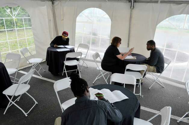 BurgerFi general manager, Meredith Mercier, background third from left, interviews Denzel Grimes during a job fair on Tuesday, June 30, 2015, in Latham, N.Y.  The business plans to open by end of the month.  Potential hires can stop by the location at 860 New Loudon Road from 9am to 5pm Monday through Friday to apply for one of 50 positions the company is looking to fill.    (Paul Buckowski / Times Union) Photo: PAUL BUCKOWSKI / 00032440A