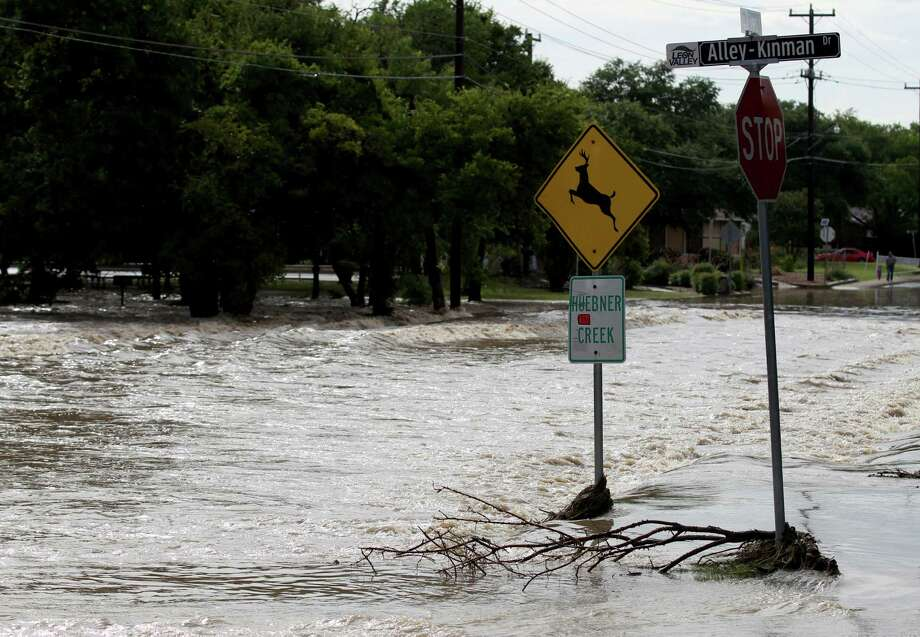 Rain water washes over Alley-Kinman Dr. near Huebner Creek and Raymond Rimkus Park in Leon Valley Tuesday.  Flash flooding closed several roads in the area with one high water rescue off of Huebner Rd. and Southwell Rd. on the Northwest side of San Antonio. Photo: Kin Man Hui / San Antonio Express-News
