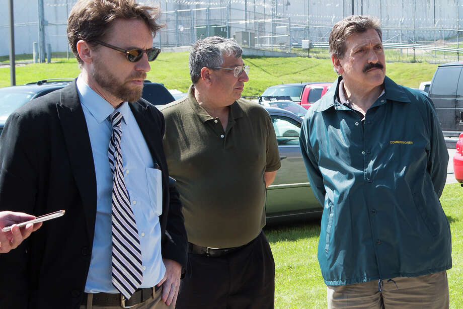 ADDS ID OF MAN AT RIGHT - In a Saturday, June 6, 2015 photo, Clinton Correctional Superintendent Steven Racette, center, listens to Gov. Andrew Cuomo speak during a press conference in Dannemora, N.Y. Officials said Tuesday, June 30, 2015, that Racette and his deputy in charge of security are among 12 more staff who have been put on administrative leave during the investigation into David Sweat and Richard Matt's escape from the maxiumum-security Clinton Correctional Facility. Acting State Department of Corrections and Community Supervision Commissioner Anthony Annucci is at right. (Gabe Dickens/The Press-Republican via AP) Photo: Gabe Dickens, MBO / Associated Press / The Press-Republican