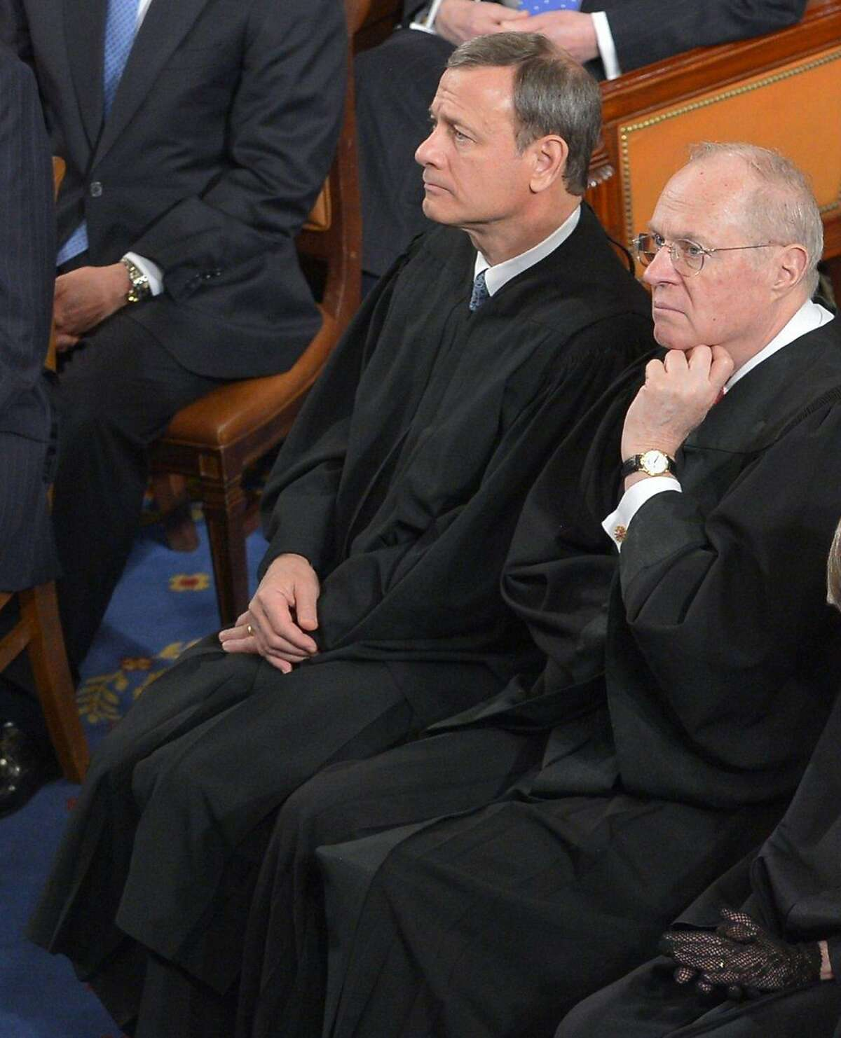 """(FILES) This February 12, 2013 file photo shows US Supreme Court Chief Justice John Roberts and Justice Anthony Kennedy(R)as they listen to US President Barack Obama deliver his State of the Union address before a joint session of Congress at the Capitol in Washington. He was appointed in the 1980s under the conservative presidency of Ronald Reagan, but Supreme Court Justice Anthony Kennedy has gone on to become perhaps the most important gay rights supporter in the American legal system.The gray-haired 78-year-old cemented that position June 26, 2015 when he wrote the majority opinion for the five judges -- or justices as they are known -- who ruled to allow gay marriage across the United States. """"No union is more profound than marriage for it embodies the highest ideals of love, fidelity, devotion, sacrifice and family,"""" Kennedy said, his deep voice resonating around the solemn surroundings of the Supreme Court. AFP PHOTO/Mandel NGANMANDEL NGAN/AFP/Getty Images"""