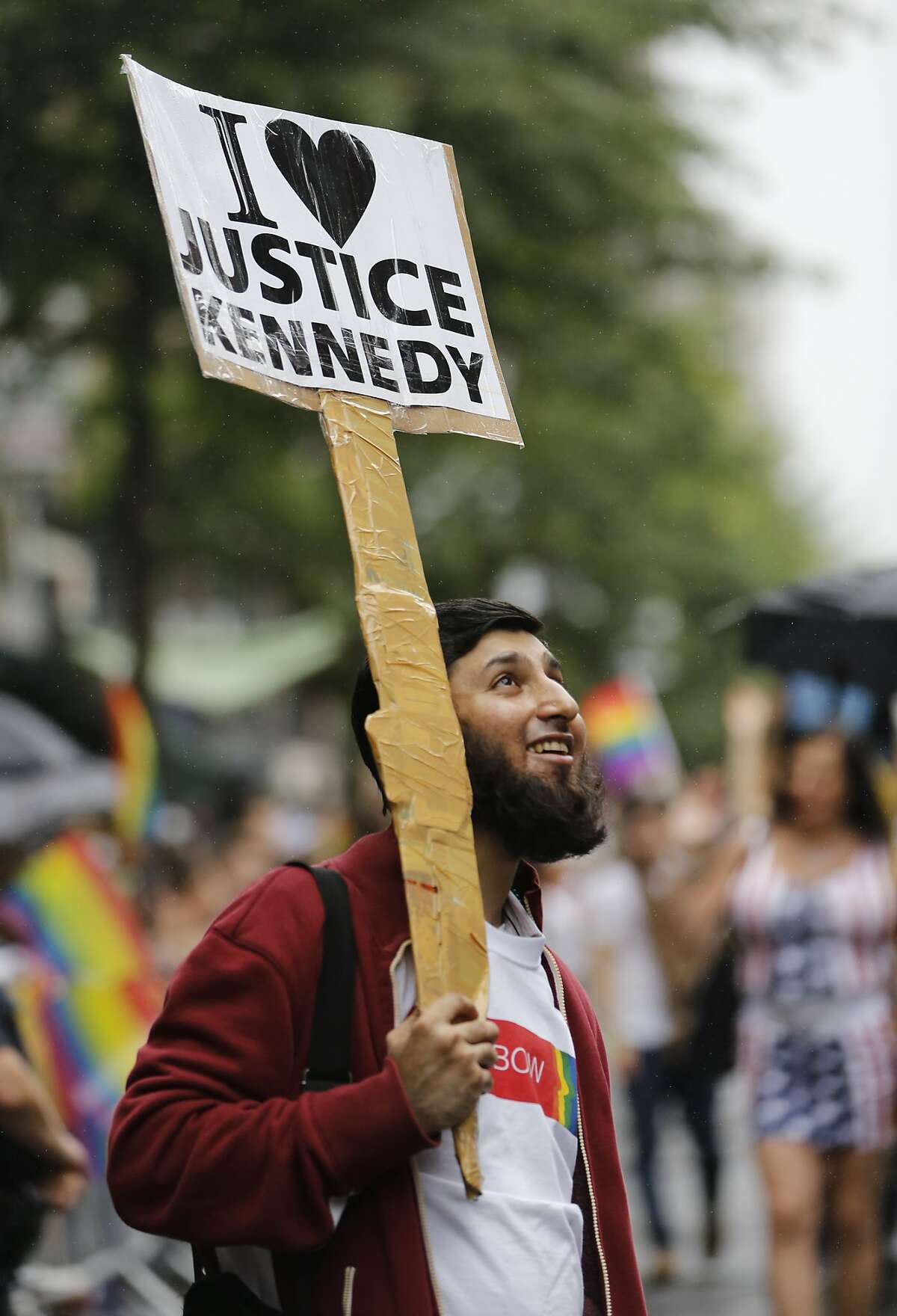 Indian immigrant Anan Farooqi, who said he is glad he lives in the United States, holds a sign professing his love of Supreme Court Justice Anthony M. Kennedy during the Heritage Pride March in New York, Sunday, June 28, 2015. Large turnouts were expected for gay pride parades across the U.S. following the landmark Supreme Court ruling that said gay couples can marry anywhere in the country. (AP Photo/Kathy Willens)