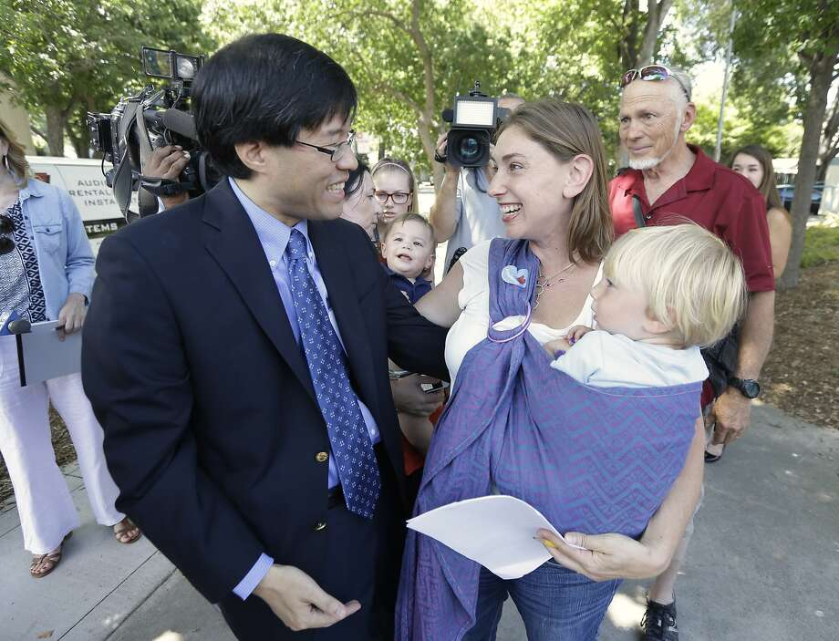Sen. Richard Pan, D-Sacramento, is thanked by Leah Russin, holding her son Leo, 21 months, after Pank's measure requiring nearly all California school children to be vaccinated in response to a measles outbreak in Disneyland last year, was signed by Gov. Jerry Brown, Tuesday, June 30, 2015, in Sacramento,Calif.  The bill, SB277, gives  California one of the toughest vaccination laws in the country. (AP Photo/Rich Pedroncelli) Photo: Rich Pedroncelli, Associated Press