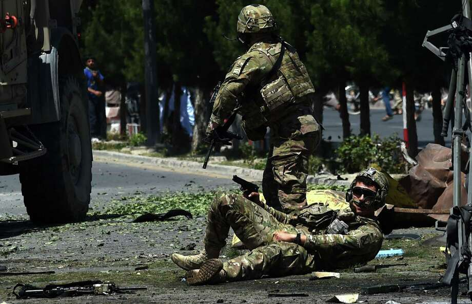 An injured NATO soldier lies on the ground after the suicide car bomb attack that targeted foreign military vehicles in the Afghan capital of Kabul. A spokesman said no NATO troops were killed. Photo: Wakil Kohsar /Getty Images / AFP