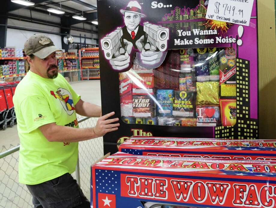 Bob Fikes straightens a display of fireworks Tuesday at Top Dog Fireworks Warehouse in Tomball. Photo: Billy Smith II, Staff / © 2015 Houston Chronicle