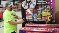 Bob Fikes straightens a display of fireworks Tuesday at Top Dog Fireworks Warehouse in Tomball.