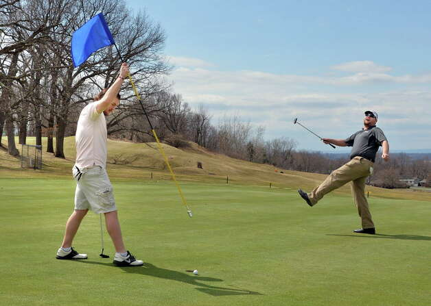 Golfer Caleb Gleason, left, of Watervliet lifts the flag as Ross Martin of Troy reacts to a nearly perfect putt as Frear Park Municipal Golf Course opens for the season Friday, April 11, 2014, in Troy, NY.  (John Carl D'Annibale / Times Union) Photo: John Carl D'Annibale / 00026450A
