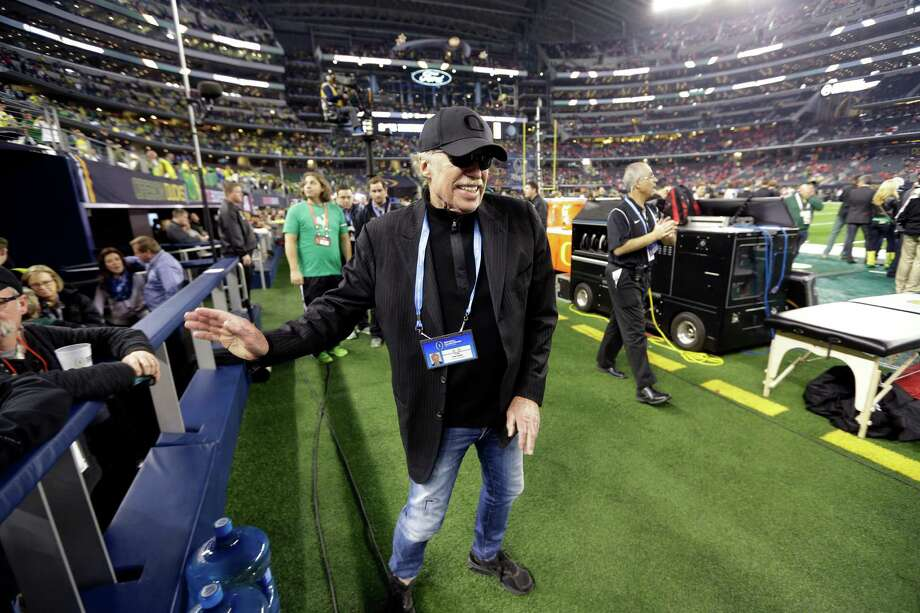 Phil Knight walks near the field before the NCAA college football playoff championship game early this year between Ohio State and Oregon in Arlington. Knight said Tuesday he plans to step down as chairman of Nike.  Photo: David J. Phillip, STF / AP