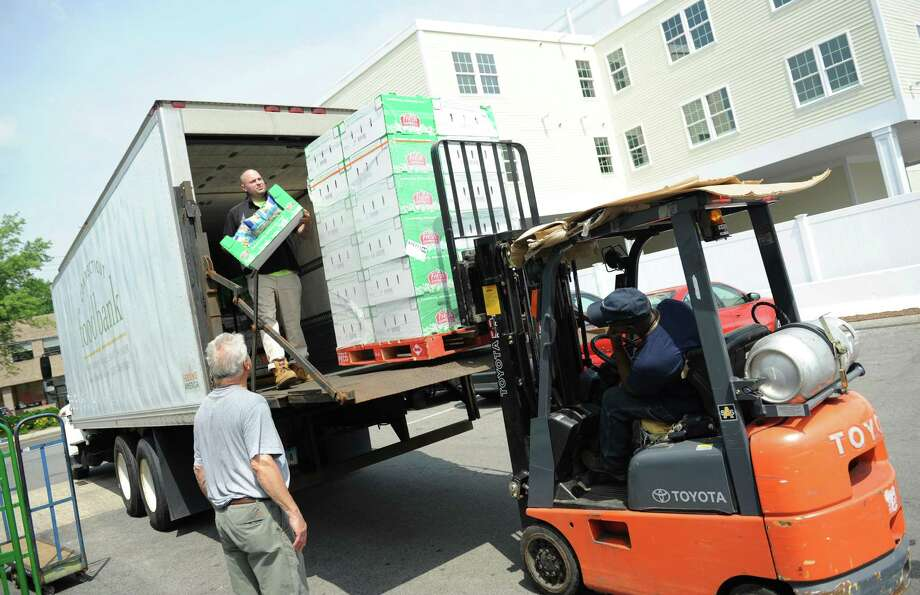 Connecticut Food Bank employee Mike Patterson unloads food from his truck as volunteer Gary Bologna, left, of Stamford, and Warehouse Manager Willie Johnson help out at the Food Bank of Lower Fairfield County in Stamford. Photo: Tyler Sizemore / Hearst Connecticut Media / Greenwich Time