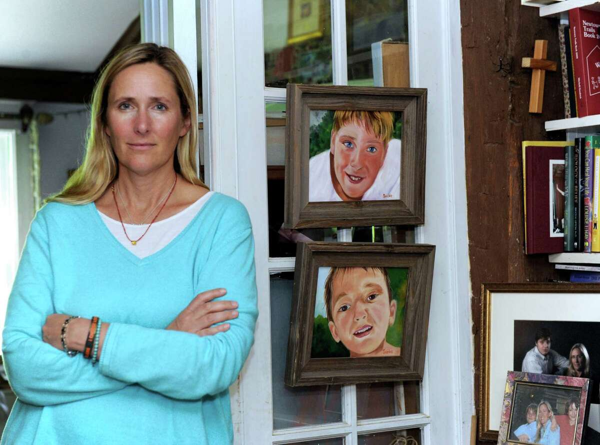 Scarlett Lewis, who lost her son, Jesse, in the Sandy Hook shooting is photographed next to paintings she made of her sons J.T. and Jesse in her home in Sandy Hook.